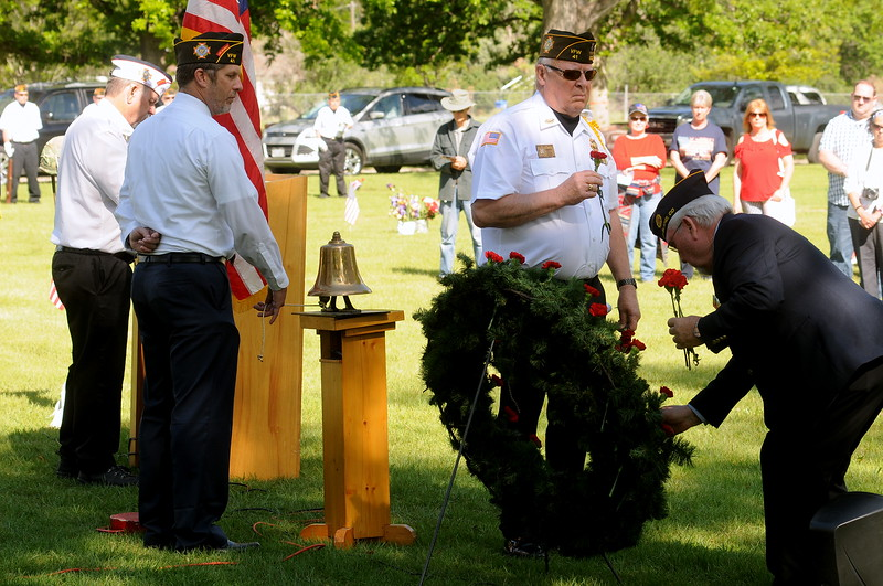 Bart Bartholomew, right, and Max DeCamp place carnations on a wreath for each of the 20-plus members of the Associated Veterans of Loveland who have died in the past year, during the Memorial Day service at Loveland Burial Park on Monday, May 29, 2017. (Photo by Craig Young / Loveland Reporter-Herald)