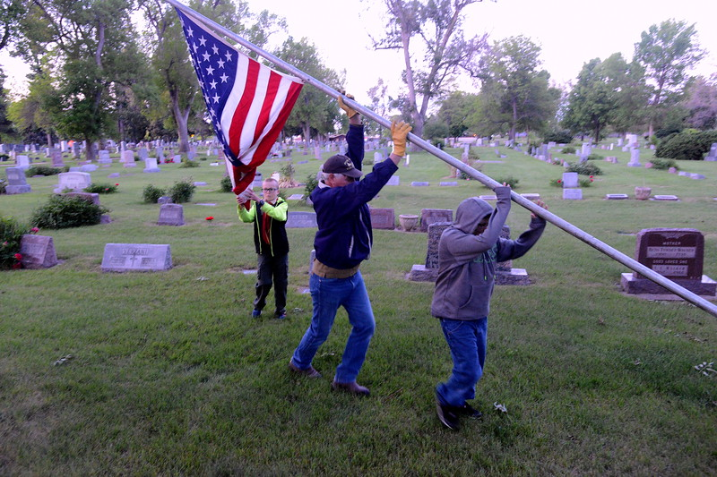 Gene Turlak and an unidentified Boy Scout raise a flagpole Monday morning, May 29, 2017, at Loveland Burial Park and Cole Ingraham, 10, holds the flag as it unfurls. Turlak brought his grandson, 12-year-old Alexander Byrd, to help with the Memorial Day project. (Photo by Craig Young / Loveland Reporter-Herald)