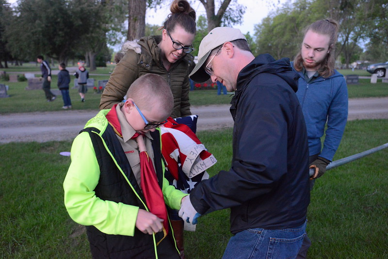 Boy Scout Cole Ingraham, 10, his mom, Tracey, and Eric Clark work to attach an American flag to a flagpole at Loveland Burial Park on Monday morning, May 29, 2017, as Evan Clark, right, holds the pole. (Photo by Craig Young / Loveland Reporter-Herald)