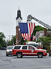 HOLLY PELCZYNSKI - BENNINGTON BANNER Members of the Hoosick Falls Fire Department raise the american flag on Main St. in Hoosick Falls town Center in remembrance and honor of Memorial Day, Monday May 28th.