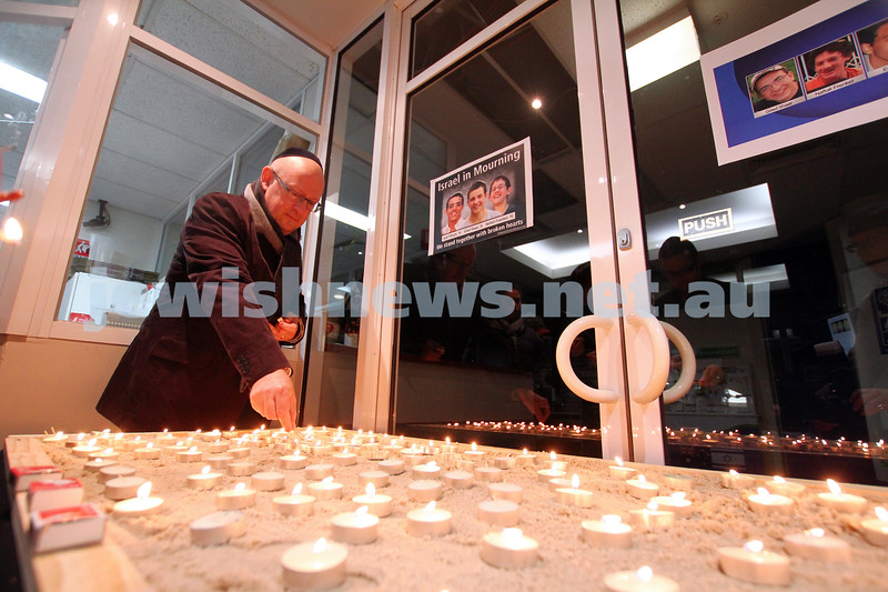 1-7-14. Memorial service at Beth Weizmann for the murdered Israeli teenagers Naftali Frenkel, Gilad Shaar and Eyal Yifrach. David Marlow, JCCV,  lighting a candle. Photo: Peter Haskin