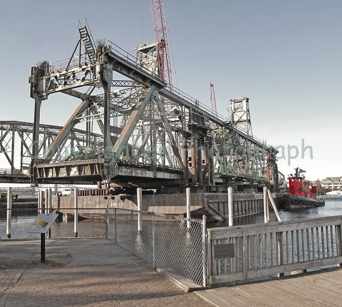 "Center span of Memorial Bridge at rest near Prescott Park prior to its float-off departure for a Quincy, Mass salvage yard.The story is that when the folks at the"" scrap piles pier "" learned of the lead paint and asbestos which adorned the center span, they asked that it be relocated.-February 13, 2012"