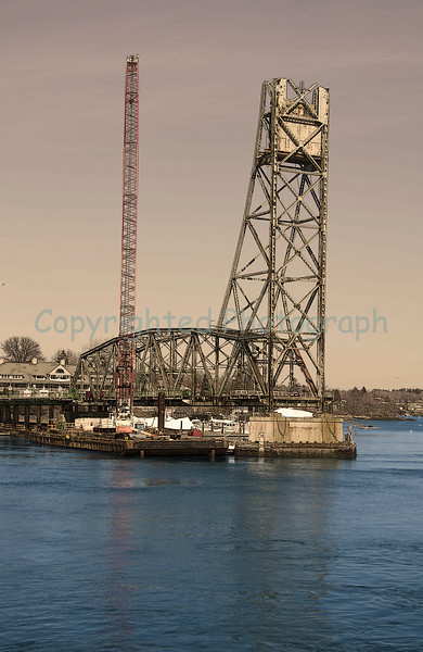 While Excalibur awaits repairs, the smaller crawler crane barge,the Amquip Crane, is moved across the river to the Kittery tower where further deconstruction will continue.-March 8, 2012