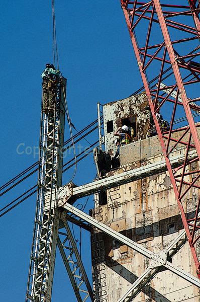 Having climbed up the tallest structural member of the Portsmouth tower, a construction worker attaches the crane's hoisting cable to this vertical section which will be cut along its base and removed. The crossmember will be removed as well prior to lifting off the first section of counterweight.-March 23, 2012 (bright sun, blue sky and nearly 80 degrees,as evidenced by the person in the t-shirt)
