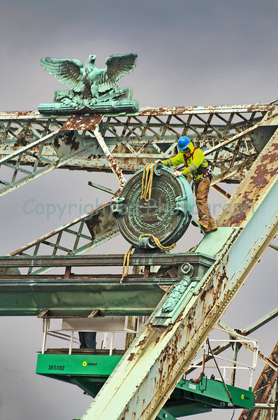 Portsmouth side bridge construction worker prepares the NH State Plaque for removal.-February 27,2012