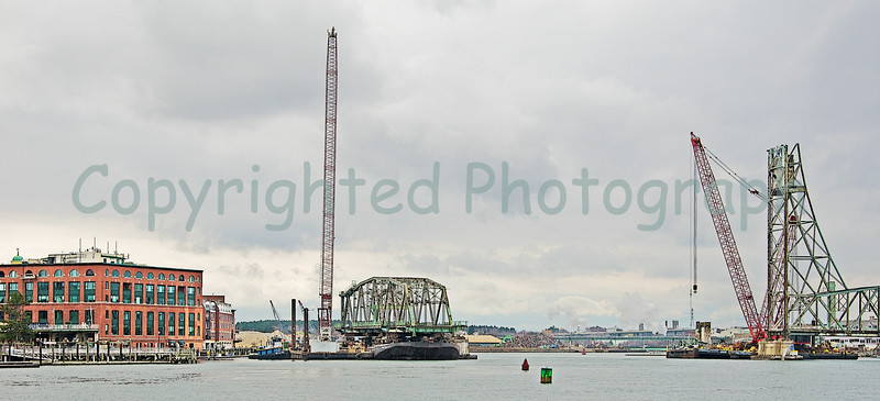 The Cape Cod, the transport barge carrying the south span, is tied off to the Amquip Crane  barge and then both are pushed against the the span's former pier. When properly positioned, she will be made fast to the pier and the crawler crane barge's pilings(spuds) will be lowered into the river bottom to better anchor the pair. It is from this point(once everything is properly secured) that the Cape Cod with leave for her trip to Boston Harbor. From there the former Memorial Bridge's south span will be recycled at an Everett, Ma salvage yard.