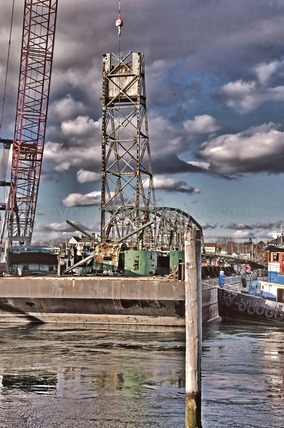 Piece by Piece,  portions of the Memorial Bridge are disassembled,and are lowered onto a barge for transport to a salvage yard.-February 28, 2012