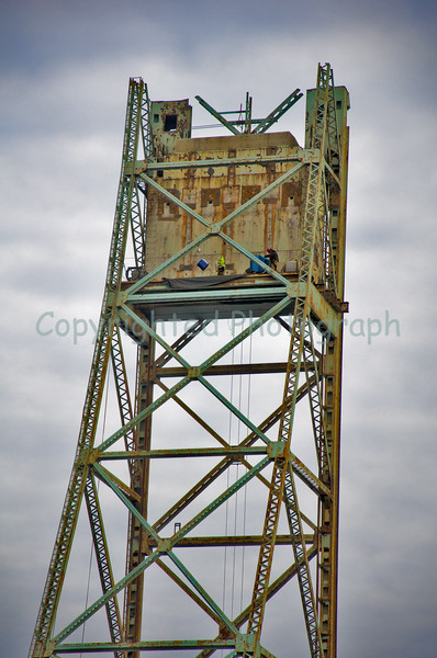 A lone worker high atop the Portsmouth Tower continues to prepare the massive counterweight for removal. The counterweight will be cut into 4 equal vertical sections prior to hoisting.-February 27, 2012