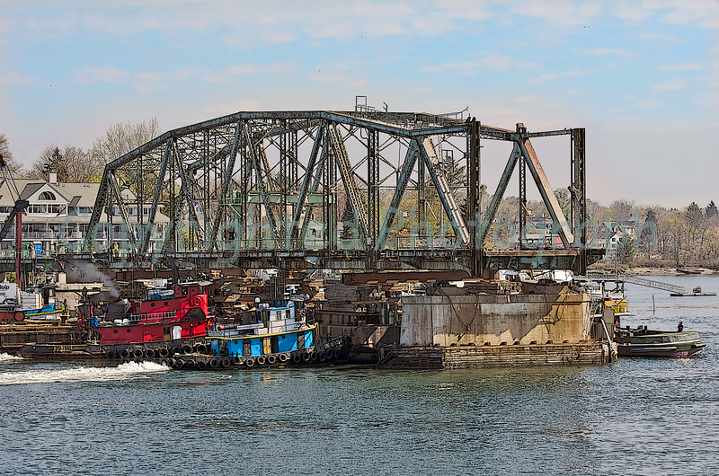 Although no evidence of any bridge activity at 0700, by 0845 the Cape Cod had been positioned under the north span(Kittery span), three tugs were in place and cutting of the last few sections of metal securing the bridge to its foundation was well underway. Here, the incoming tide has lifted the barge with span and the process of moving this section has begun. -April 21, 2012