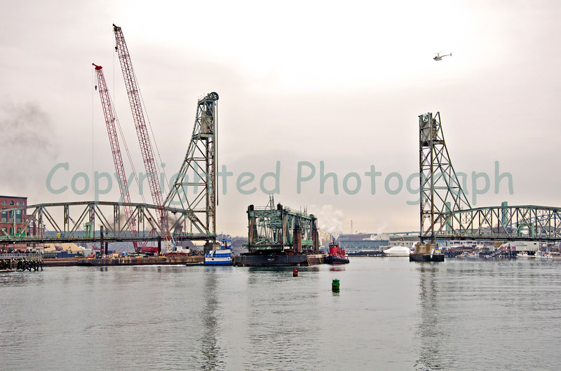 Tugs maneuver the Memorial Bridge's center span as it begins its journey to Boston Harbor. Notice the suspension cables still dangling from the Portsmouth tower, while the cables, massive sheaves and sheave covers have been removed from the Kittery tower. -February 15, 2012