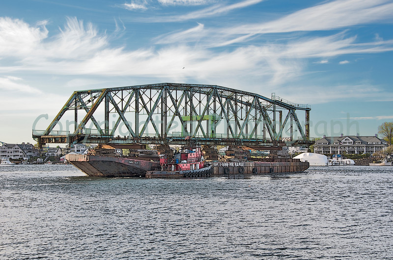 Once clear of the pier and barge that held her fast, and now in the channel, the Cape Cod barge is rotated so that she is floated stern first down the Piscataqua on her way to the open ocean. The Miss Yvette(tug in the foreground) has her tow line attached to the Cape Cod's bow, which will require another rotation before she reaches the open ocean. -April 28, 2012.