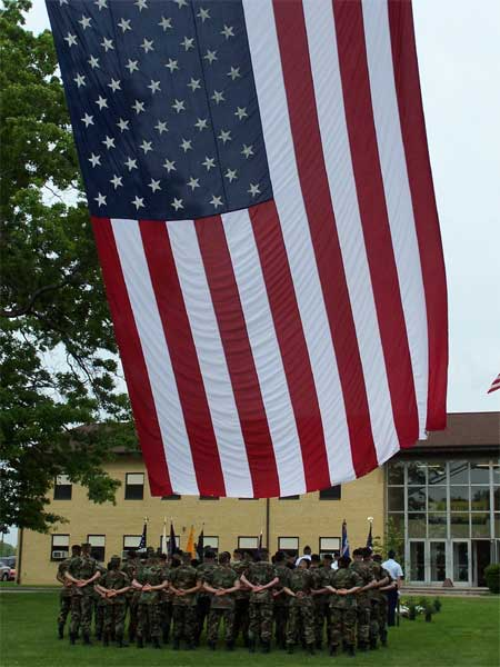 A flag flies above a formation of Soldiers from the 402nd Civil Affairs Battalion during a memorial ceremony for Spc. Charles E. Bush Jr. at the Pfc. Charles N. Deglopper U.S. Army Reserve Center, Tonawanda, N.Y.  Bush, a civil affairs Soldier, was killed Dec. 19, 2003 when his vehicle was ambushed in Balad, Iraq.