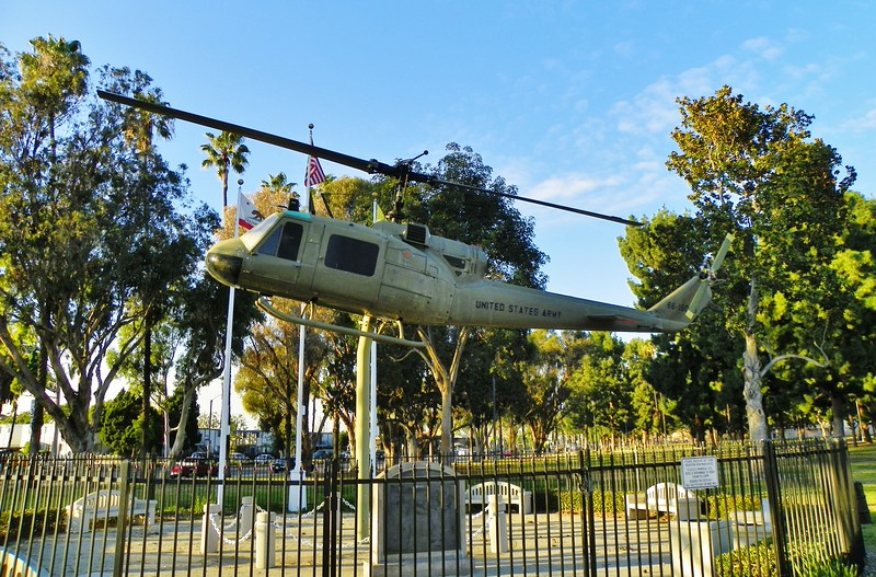 "Designed by Christopher Umana, a Long Beach City College art student, the memorial features a U.S. Army ""Huey"" . The helicopter, donated by Al Gerbino, logged more than 2,000 combat hours in Vietnam."