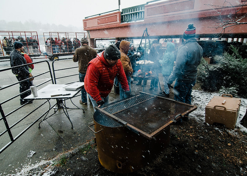 A crowd gets warm by the fire on Boulder Drive during the Memories of Main Street event in Fitchburg on Saturday, December 9, 2017. SENTINEL & ENTERPRISE / Ashley Green
