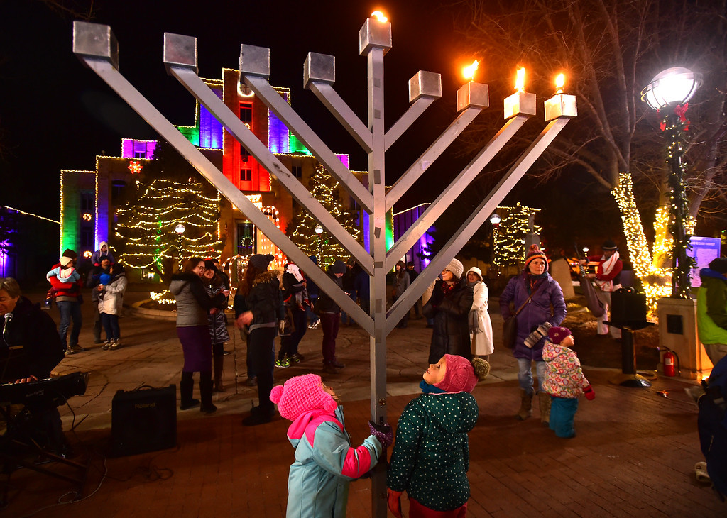 . Naomi Schare, left and Odessa Stack, gather around the lit menorah on the Pearl Street Mall on Monday evening. For more photos go to www.dailycamera.com Paul Aiken / Staff Photographer / Dec 26 2016