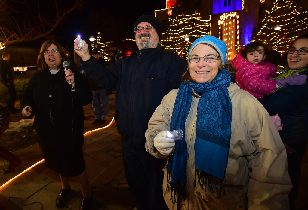 . Jerry and Marilyn Pinsker are introduced by Chany Scheiner, at left, before the lighting of the menorah  on the Pearl Street Mall on Monday evening. For more photos go to www.dailycamera.com Paul Aiken / Staff Photographer / Dec 26 2016