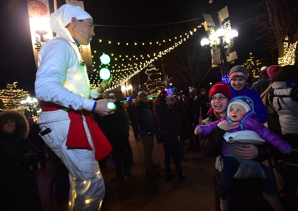 . Melissa Ginsburg and her daughter Carly Stocker watch performer Sven Jorgensen before the menorah lighting on the Pearl Street Mall on Monday evening. For more photos go to www.dailycamera.com Paul Aiken / Staff Photographer / Dec 26 2016
