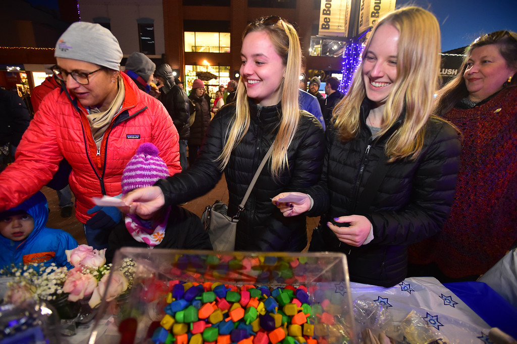 . Amanda Derdiger and her sister Samara try to guess how many dreidel are in a box during ceremonies for the menorah lighting on the Pearl Street Mall on Monday evening. For more photos go to www.dailycamera.com Paul Aiken / Staff Photographer / Dec 26 2016