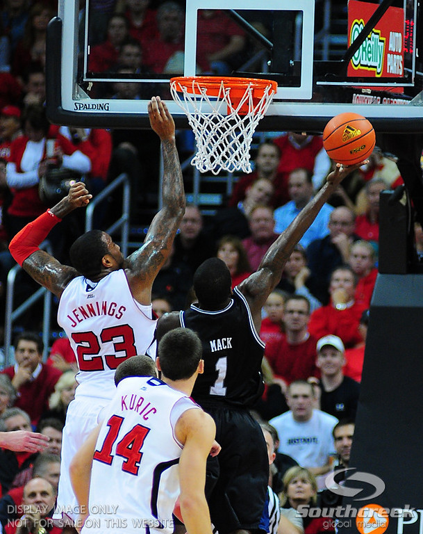 Butler guard Shelvin Mack (1) uses the rim to get around Louisville forward Terrence Jennings (23) during the game.  Louisville leads Butler 41-23 at the half  at the KFC Yum Center in Louisville, Kentucky.