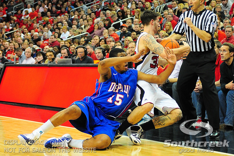 DePaul Blue Demons forward Moses Morgan (15) and Louisville Cardinals guard Mike Marra (33) go after a loose ball.  (15) Louisville Cardinals tied with DePaul Blue Demons 34-34 in the first half at the KFC Yum Center in Louisville, Kentucky.