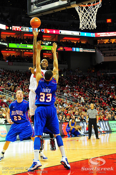 Louisville Cardinals forward Terrence Jennings (23) goes over DePaul Blue Demons center Krys Faber (33).  (15) Louisville Cardinals tied with DePaul Blue Demons 34-34 in the first half at the KFC Yum Center in Louisville, Kentucky.