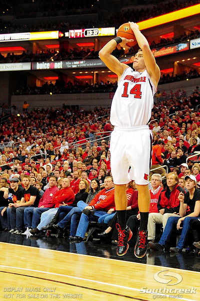 Louisville guard Kyle Kuric (14) shoots a three.  (17) Louisville defeated Marquette 71-70 at the KFC Yum Center in Louisville, Kentucky.