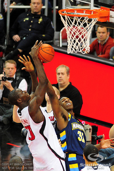 Louisville center Gorgui Dieng (10) goes up over Marquette forward Jae Crowder (32) for the rebound.  (17) Louisville defeated Marquette 71-70 at the KFC Yum Center in Louisville, Kentucky.