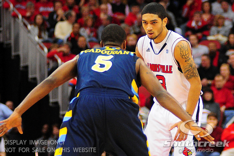 Louisville guard Peyton Siva (3) with an intense look while Marquette guard Junior Cadougan (5) plays defense.  (17) Louisville defeated Marquette 71-70 at the KFC Yum Center in Louisville, Kentucky.