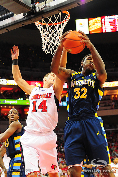 Marquette forward Jae Crowder (32) comes down with the rebound over Louisville guard Kyle Kuric (14).   Marquette leads (17) Louisville 36-31 at the half at the KFC Yum Center in Louisville, Kentucky.