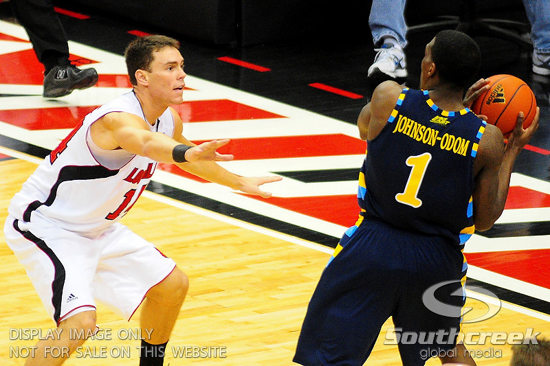 Louisville guard Kyle Kuric (14) guards Marquette guard Darius Johnson-Odom (1).  (17) Louisville defeated Marquette 71-70 at the KFC Yum Center in Louisville, Kentucky.