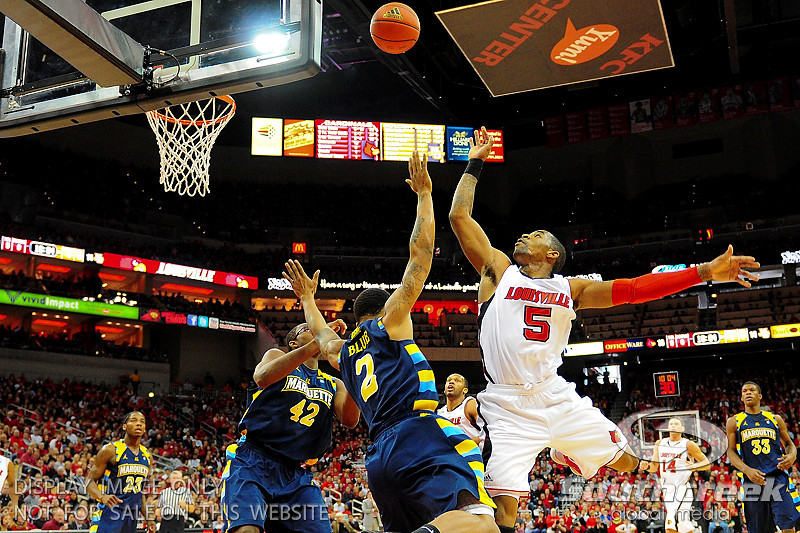 Louisville guard Chris Smith (5) puts a shot up over Marquette guard Vander Blue (2) and Marquette center Chris Otule (42).  (17) Louisville defeated Marquette 71-70 at the KFC Yum Center in Louisville, Kentucky.