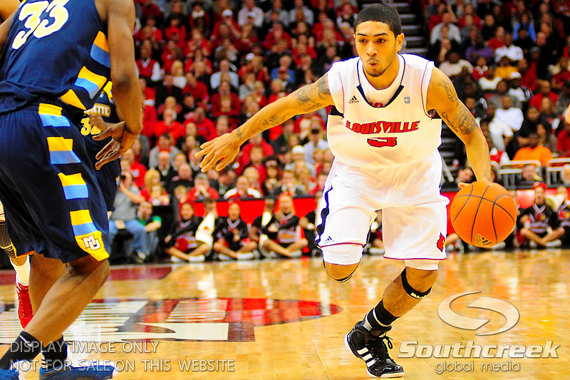 Louisville guard Peyton Siva (3) pushes the ball up court.  (17) Louisville defeated Marquette 71-70 at the KFC Yum Center in Louisville, Kentucky.