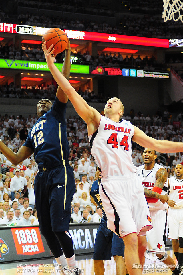 Louisville Cardinals forward Stephan Van Treese (44) battles Pittsburgh Panthers guard Ashton Gibbs (12) for the rebound.  (16) Louisville Cardinals lead(4) Pittsburgh Panthers in the first half at the KFC Yum Center in Louisville, Kentucky.