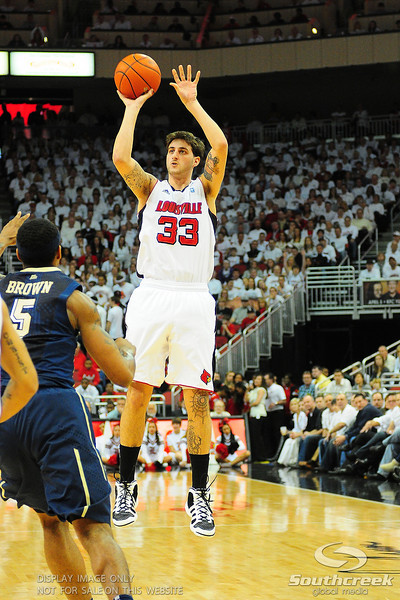 Louisville Cardinals guard Mike Marra (33) hits a three.  (16) Louisville Cardinals lead  (4) Pittsburgh Panthers in the first half at the KFC Yum Center in Louisville, Kentucky.