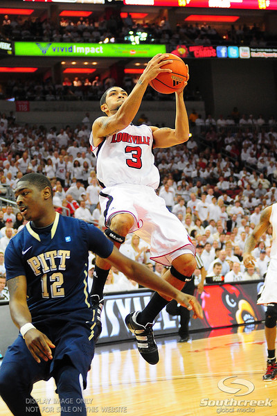 Louisville Cardinals guard Peyton Siva (3) goes up strong over Pittsburgh Panthers guard Ashton Gibbs (12).  (16) Louisville Cardinals lead  (4) Pittsburgh Panthers in the first half at the KFC Yum Center in Louisville, Kentucky.