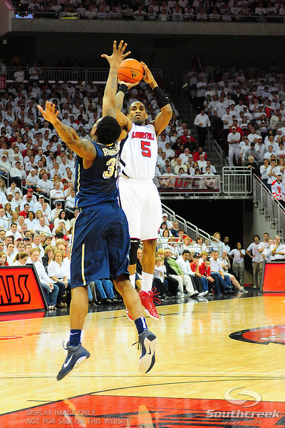 Louisville Cardinals guard Chris Smith (5) shoots a three over Pittsburgh Panthers forward Nasir Robinson (35).  (16) Louisville Cardinals (4) defeated Pittsburgh Panthers 62-59 at the KFC Yum Center in Louisville, Kentucky.