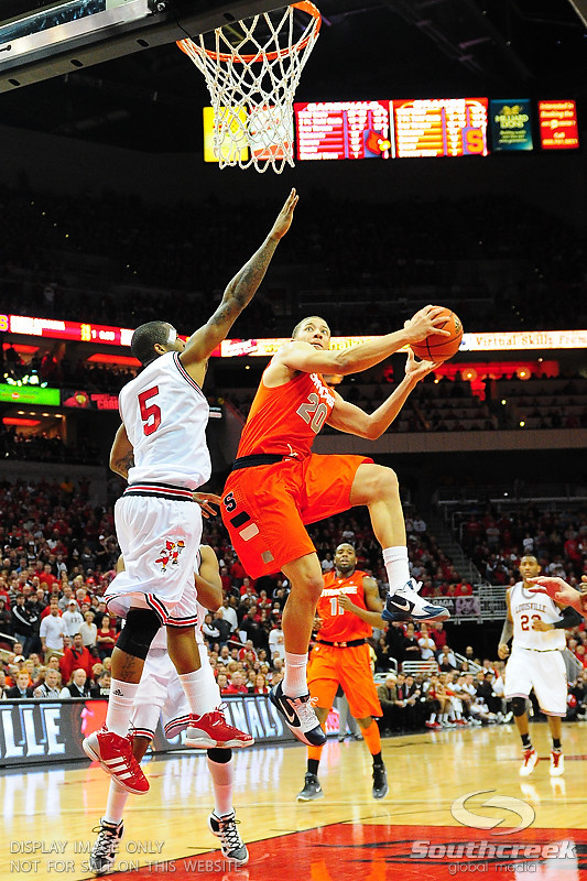 Syracuse Orange guard Brandon Triche (20) goes strong to the basket over Louisville Cardinals guard Chris Smith (5).  (16) Louisville Cardinals defeated  the (12) Syracuse Orangemen 73-69 at the KFC Yum Center in Louisville, Kentucky.