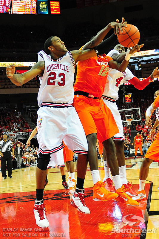 Louisville Cardinals forward Terrence Jennings (23) goes up for a rebound on Syracuse Orange forward Baye Moussa Keita (12).  (16) Louisville Cardinals defeated  the (12) Syracuse Orangemen 73-69 at the KFC Yum Center in Louisville, Kentucky.