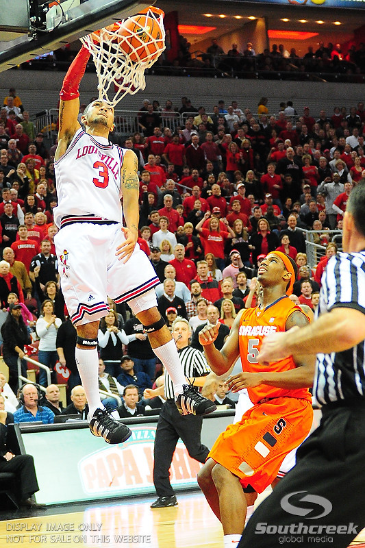 Louisville Cardinals guard Peyton Siva (3) goes up for a slam dunk over Syracuse Orange forward C.J. Fair (5).  (16) Louisville Cardinals defeated  the (12) Syracuse Orangemen 73-69 at the KFC Yum Center in Louisville, Kentucky.