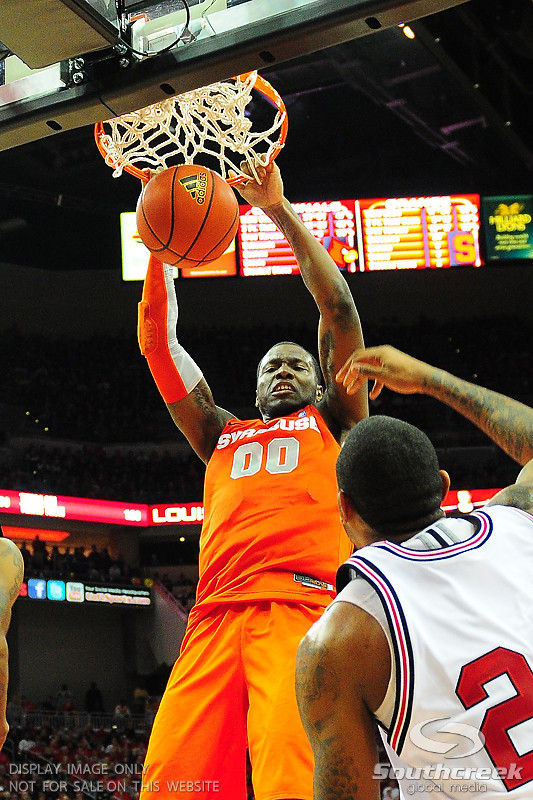 Syracuse Orange forward Rick Jackson with a slam dunk over Louisville Cardinals forward Terrence Jennings (23).  (16) Louisville Cardinals defeated  the (12) Syracuse Orangemen 73-69 at the KFC Yum Center in Louisville, Kentucky.