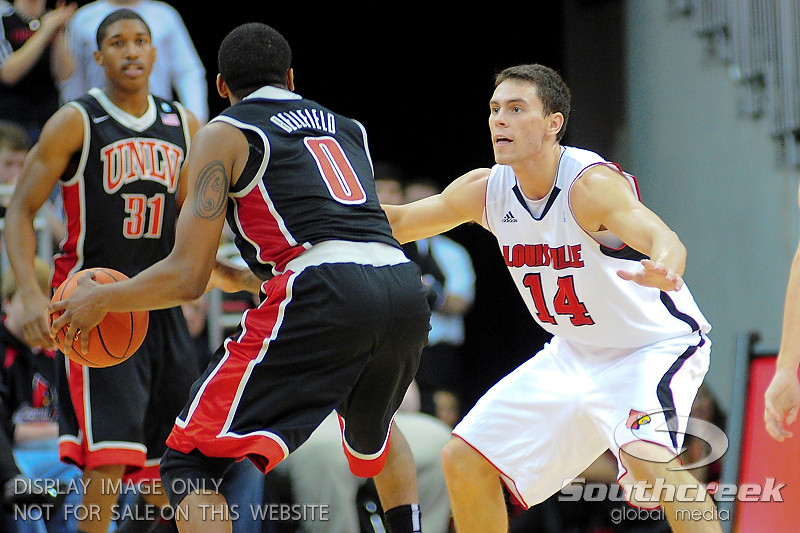 Louisville Cardinals guard Kyle Kuric (14) pressures UNLV Rebels guard Oscar Bellfield (0).  Louisville Cardinals defeated UNLV Rebels 77 - 69 at the KFC Yum Center in Louisville, Kentucky.