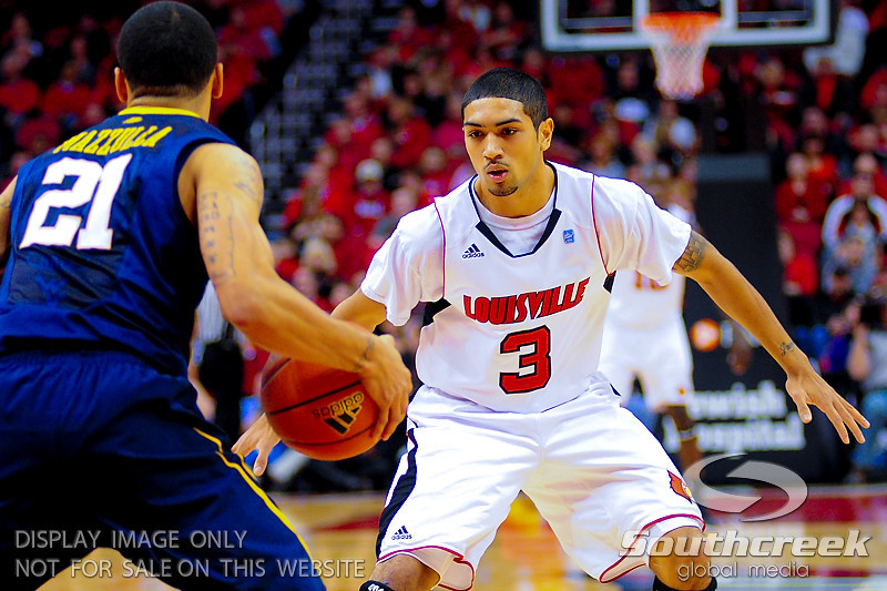 Louisville Cardinals guard Peyton Siva (3) guards West Virginia Mountaineers guard Joe Mazzulla (21) at the KFC Yum Center in Louisville, Kentucky.
