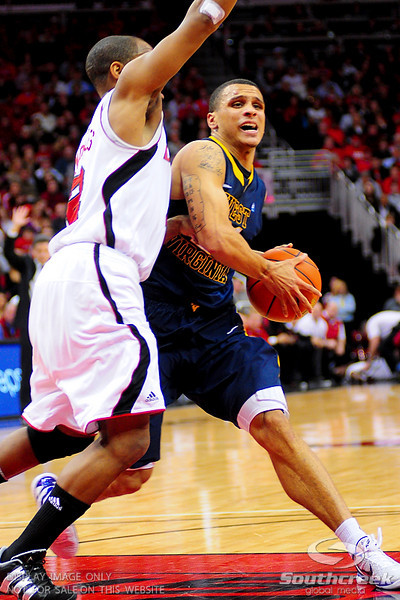 West Virginia Mountaineers guard Joe Mazzulla (21) drives past Louisville Cardinals guard Preston Knowles (2).  Louisville Cardinals defeated West Virginia Mountaineers 55-54  at the KFC Yum Center in Louisville, Kentucky.