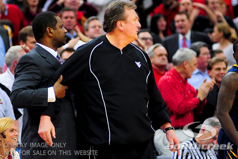 West Virginia Mountaineers associate head coach Larry Harrison holds back West Virginia Mountaineers head coach Bob Huggins after receiving a technical.  Louisville Cardinals defeated West Virginia Mountaineers 55-54  at the KFC Yum Center in Louisville, Kentucky.