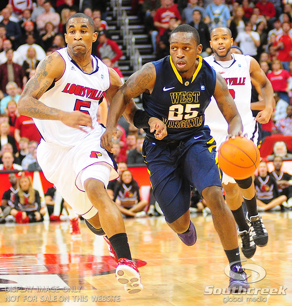 West Virginia Mountaineers guard Darryl Bryant (25) drives past Louisville Cardinals guard Chris Smith (5).  Louisville Cardinals defeated West Virginia Mountaineers 55-54  at the KFC Yum Center in Louisville, Kentucky.