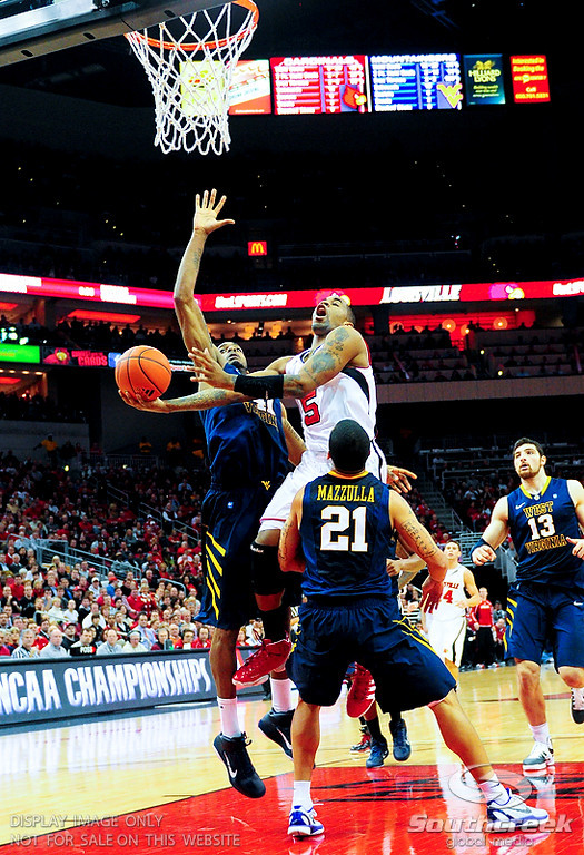 Louisville Cardinals guard Chris Smith (5) drives over West Virginia Mountaineers guard Joe Mazzulla (21) during the first half at the KFC Yum Center in Louisville, Kentucky.