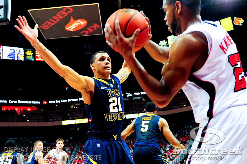 West Virginia Mountaineers guard Joe Mazzulla (21) putting pressure on Louisville Cardinals guard Preston Knowles (2) on the inbound play at the KFC Yum Center in Louisville, Kentucky.