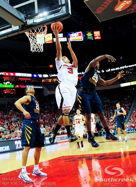 Louisville Cardinals guard Peyton Siva (3) goes strong to the basket between West Virginia Mountaineers guard Darryl Bryant (25) and West Virginia Mountaineers guard Joe Mazzulla (21) at the KFC Yum Center in Louisville, Kentucky.