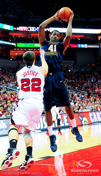West Virginia Mountaineers forward John Flowers (41) goes up strong to get a rebound over Louisville Cardinals guard Elisha Justice (22) at the KFC Yum Center in Louisville, Kentucky.