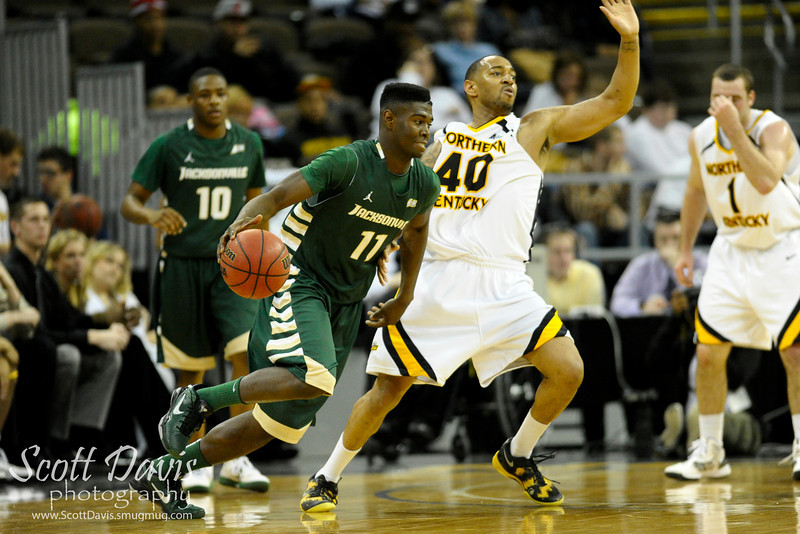 Jacksonville Dolphins guard Jarvis Haywood #11 with a charge on Northern Kentucky Norse forward Eshaunte Jones #40 during the college basketball game between Northern Kentucky Norse and  Jacksonville Dolphins .  Jacksonville Dolphins lead the Northern Kentucky Norse 30-29 at the half at The Bank of Kentucky Center in Highland Heights, Kentucky.